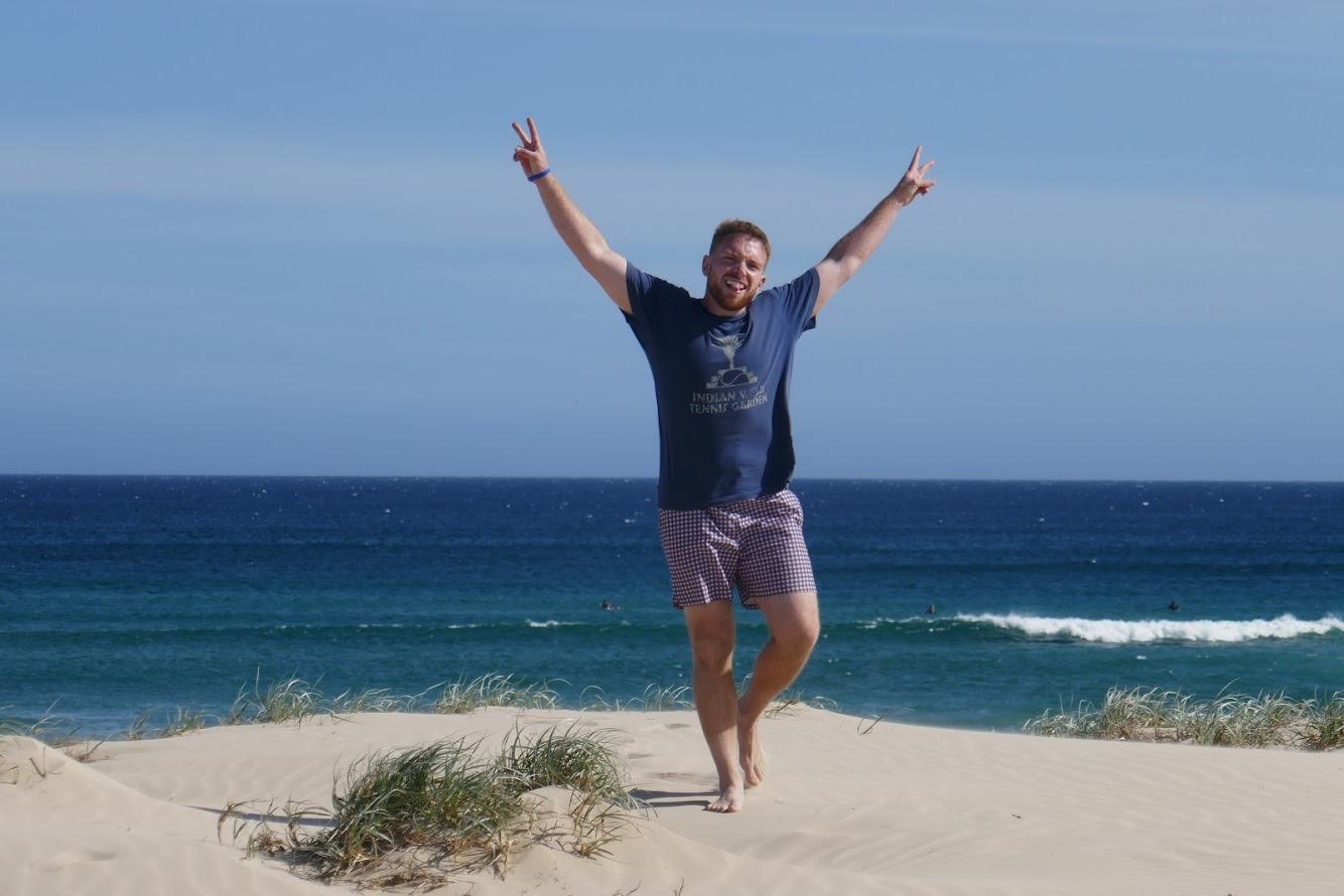 man giving peace sign at beach
