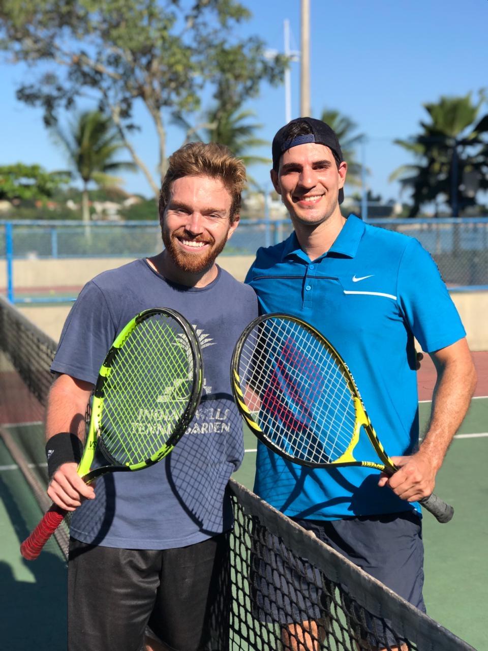 two men posing with tennis paddles