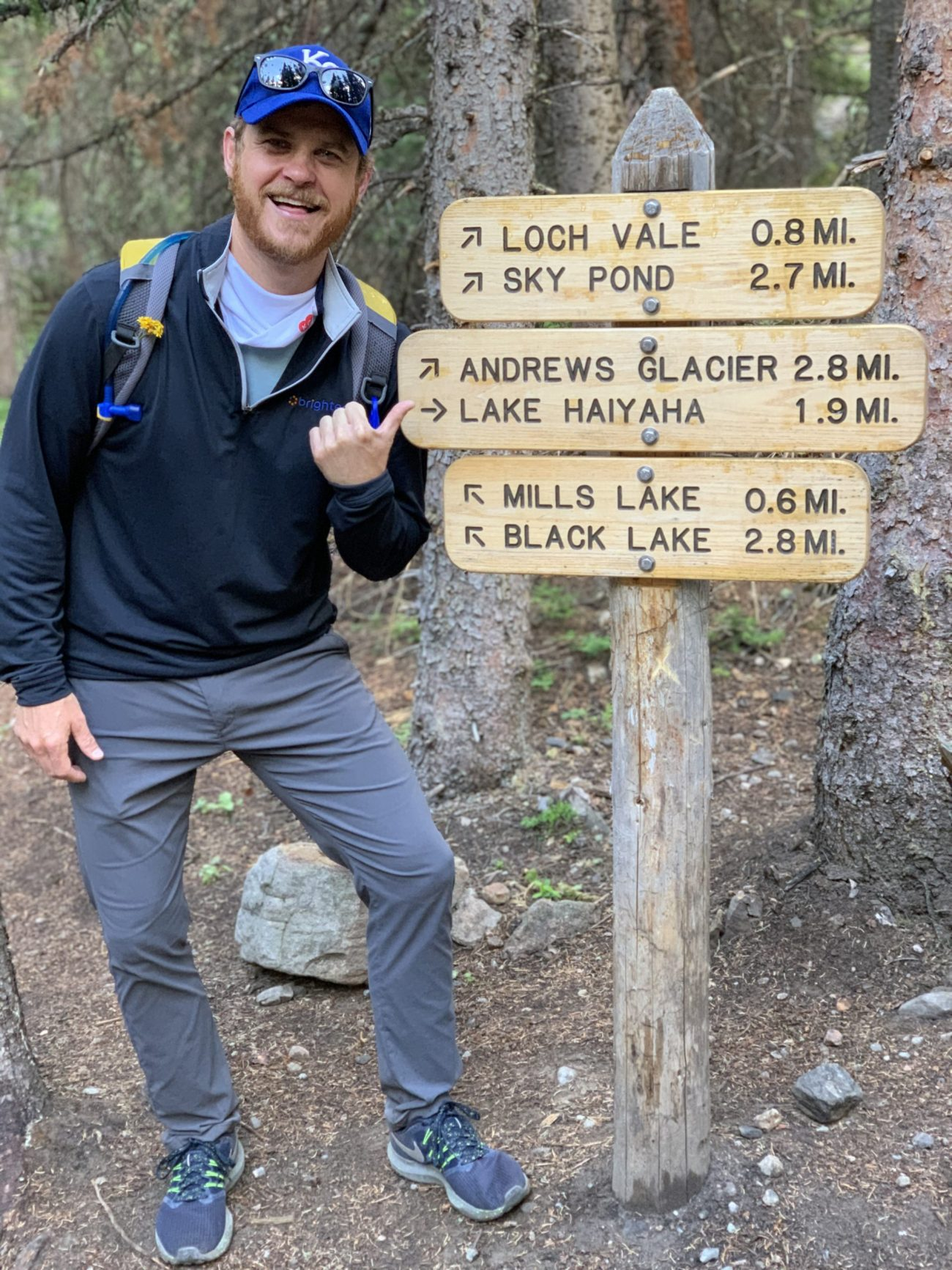 man in hiking gear pointing at trail heads