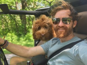 man and his dog riding in a jeep